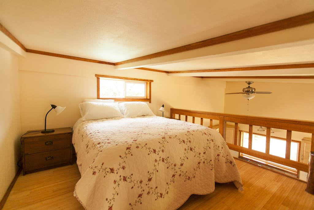 Comfortable loft double bed with low ceilings.