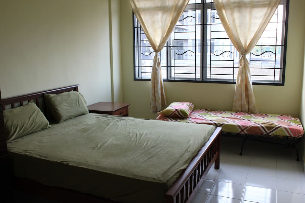 Master bedroom with 1 queen-size and 1 single bed, and attached bathroom, can fit 3 adults. The garden and sea view from the room windows.