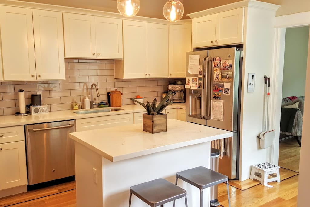 Kitchen island has seating for two, leads into TV room
