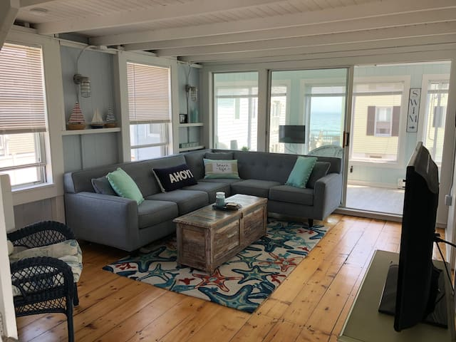 Living room view to front enclosed porch and partial ocean views. You can hear the waves