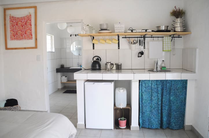 A small kitchen area comes with a mini fridge, tea kettle, hot plate, coffee, tea, sugar, and modest cooking utensils and dishes