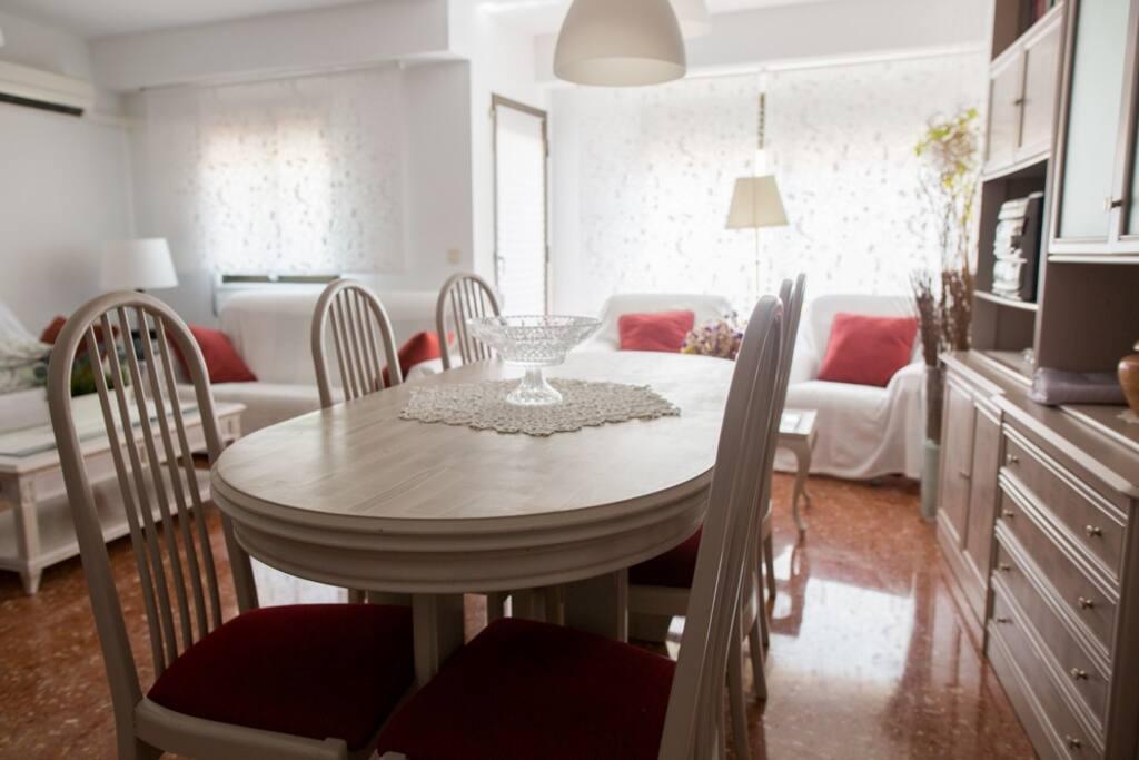 Amplio salón con una mesa de comedor grande, dos sofás y dos sillones