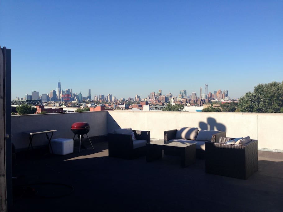 Private roof deck with seating and charcoal grill. The open views of Manhattan allow you to look out onto the new World Trade Center and the Empire State Building