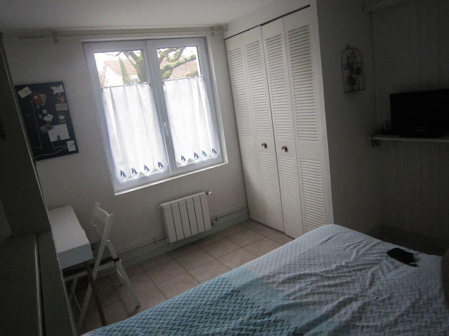Fenêtre donnant sur le jardin, placard équipé d'une penderie, coin bureau