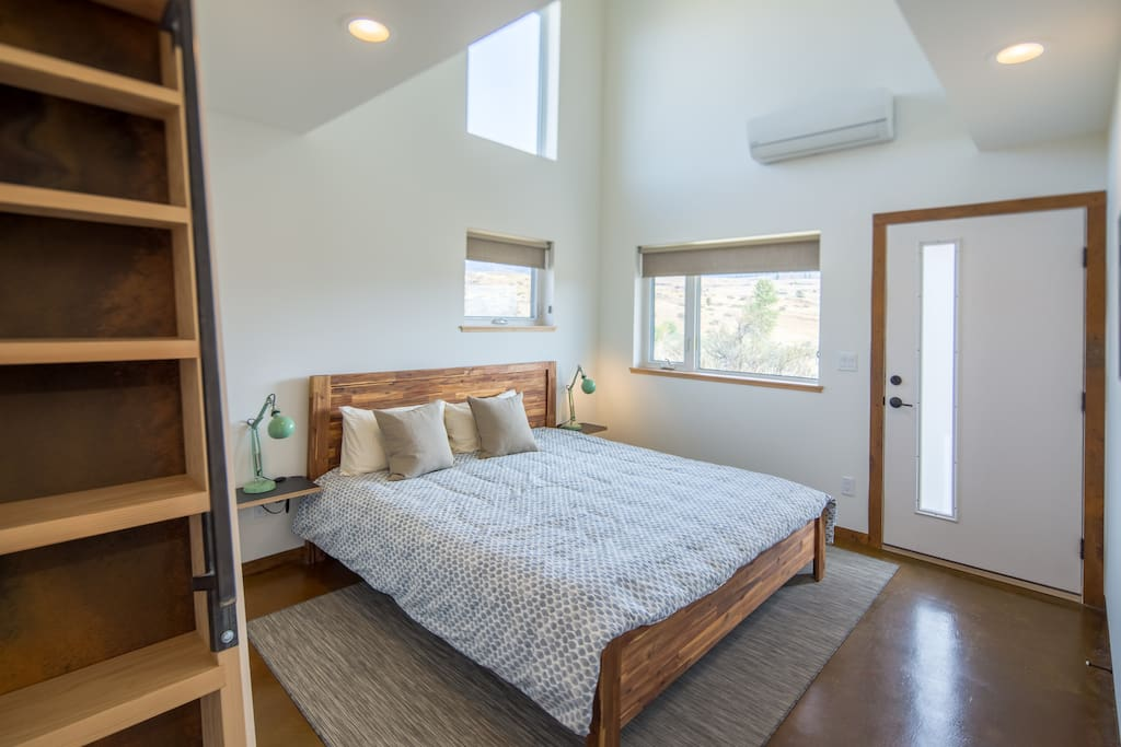 Master bedroom with luxurious king-size natural latex mattress and ladder to sleeping loft