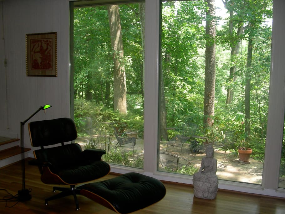A wall of windows overlooks in the living room overlooks a wooded hill that descends to a creek
