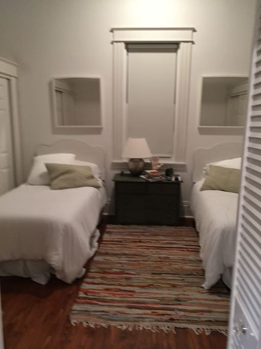 Twin beds flanked by closets.  TV across room.