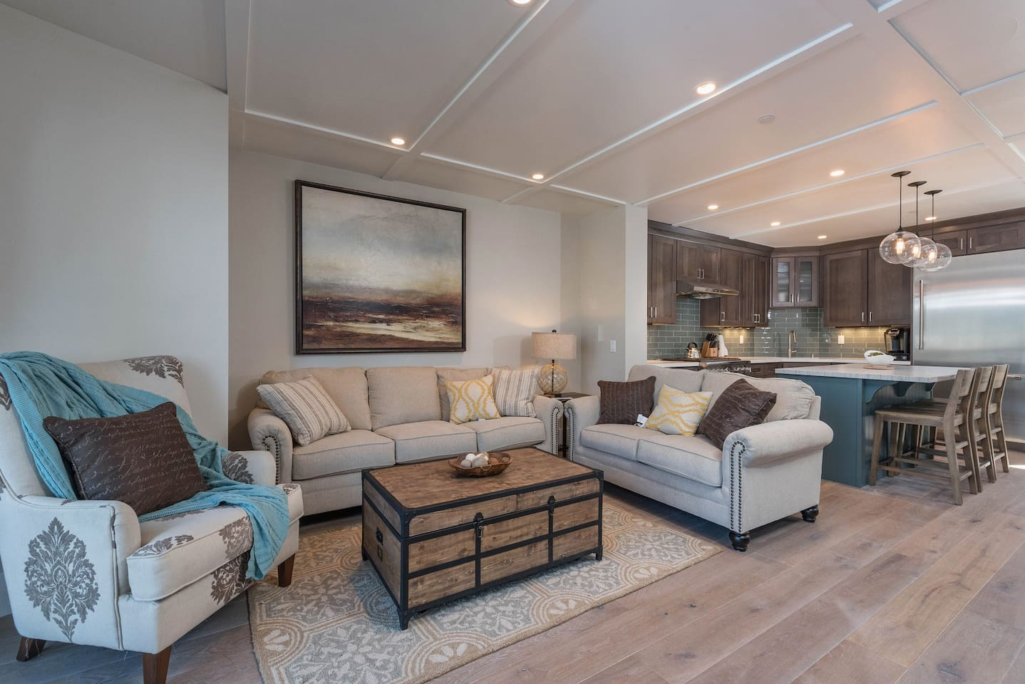 Hardwood floors frame the open-concept space, while 2 sofas and an armchair provide ample seating in the living area.