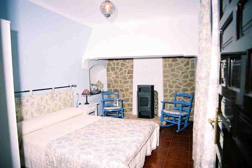 Habitación con cama de matrimonio y chimenea