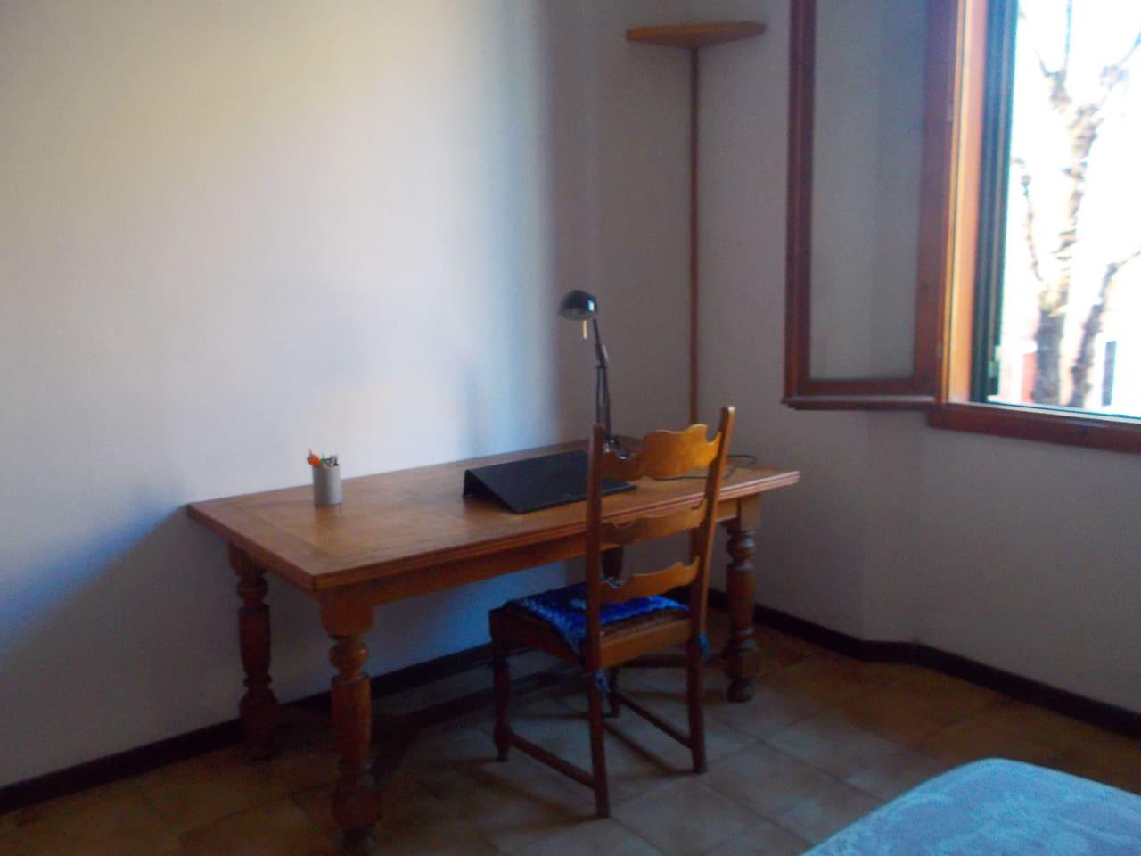 Angolo luminoso con scrivania, lampada e poggia pc