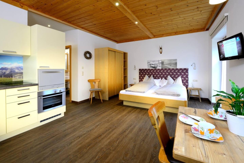 Apartment Zenzi mit Küchenzeile, Doppelbett, Schlafcouch, Eßtisch, Garderobe und Bad, sowie direkten Gartenzugang