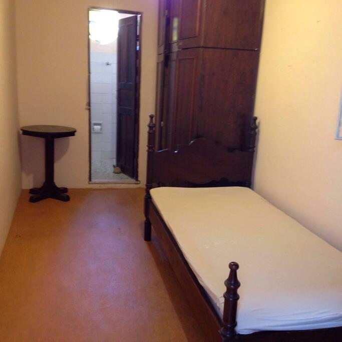 Quarto com cama de solteiro e banheiro privativo