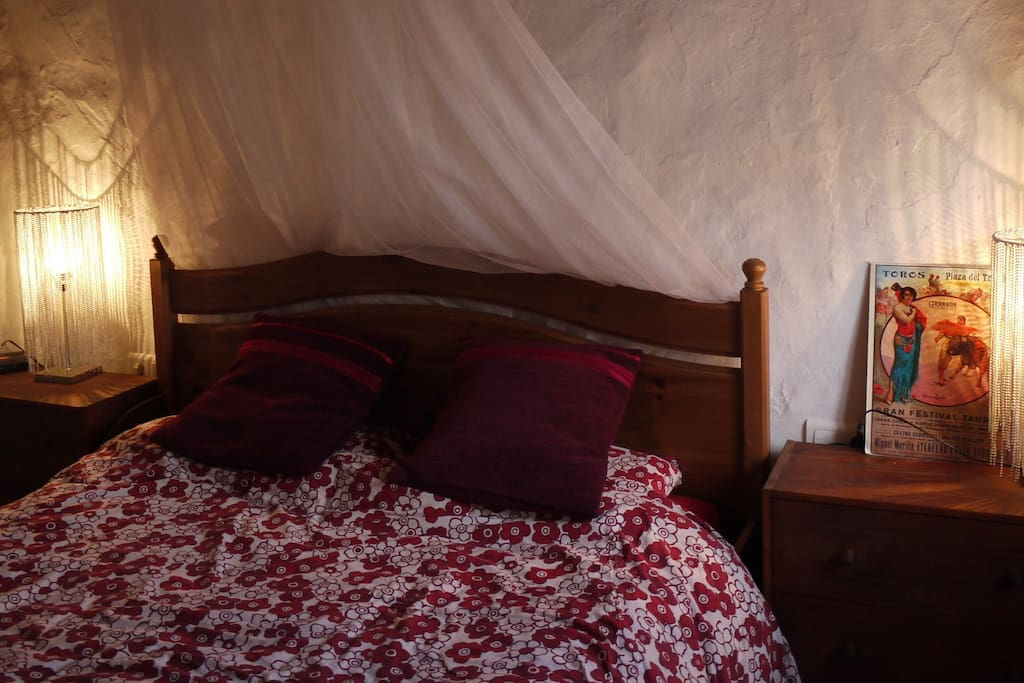 Bedroom with Moroccan lighting and comfy bed.