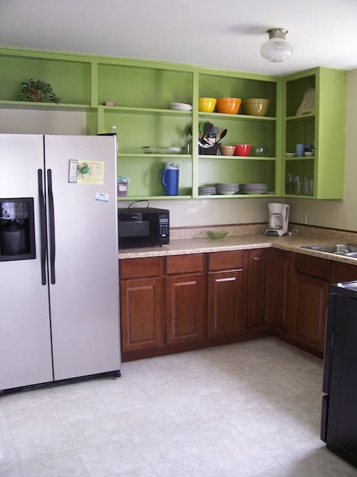 Fully-stocked kitchen with full-sized stove and refrigerator, coffee pot, coffee bean grinder, hand mixer microwave, toaster, griddle, pots and pans, baking trays (muffin, cookie, roasting), silverware and serving utensils, plates, glasses, mugs, etc.