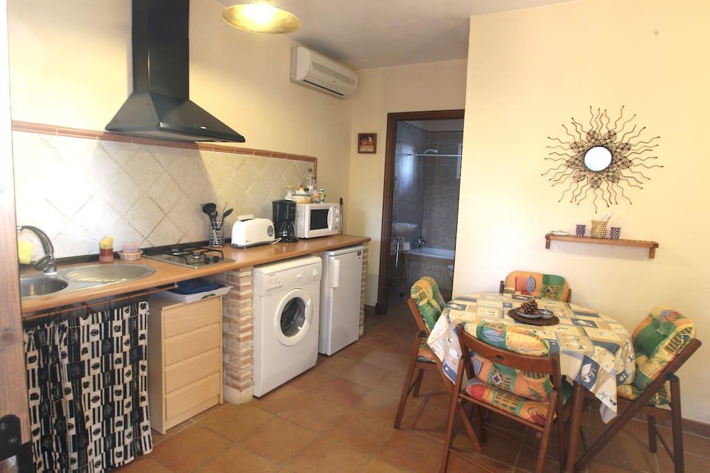 Salón-cocina con lavadora, nevera, microondas, tostadora y cafetera