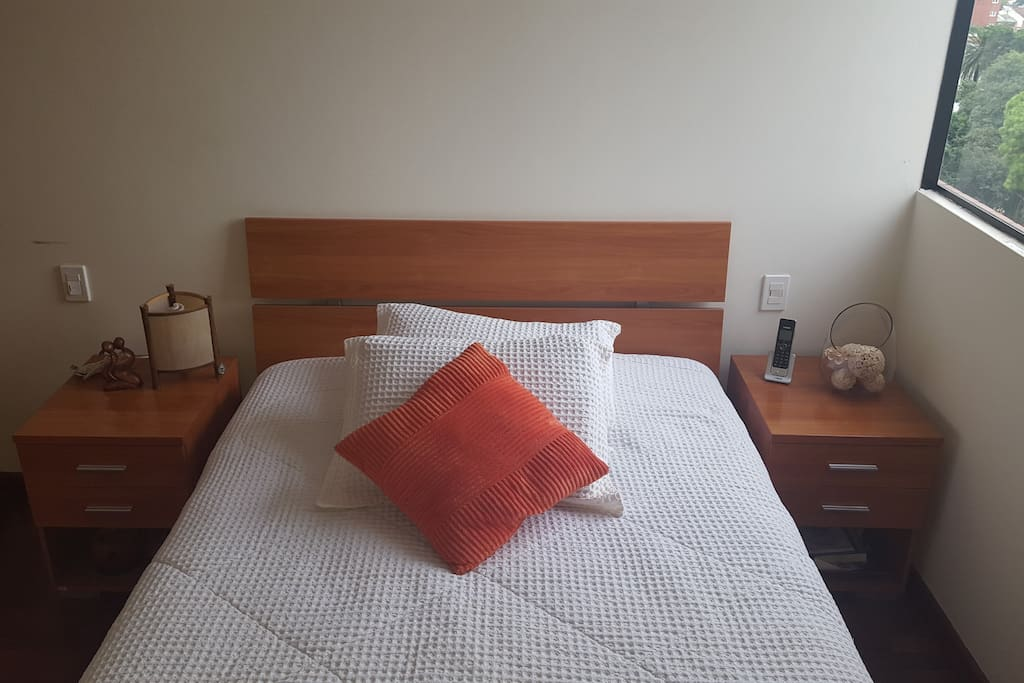 bed with 2 bedside tables and lamp