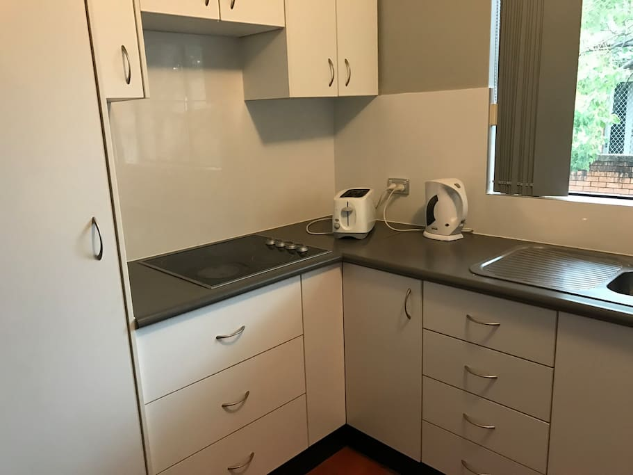 nice clean kitchen with mocrowave kettle  toaster  fridge  and all other utencils