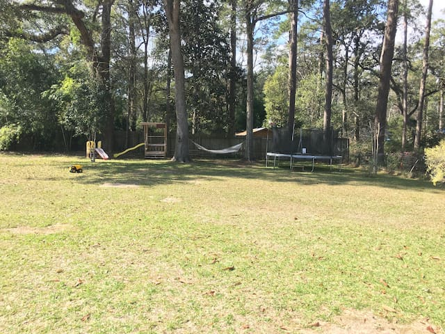 Backyard with trampoline, hammock, slides, and other outdoor toys.