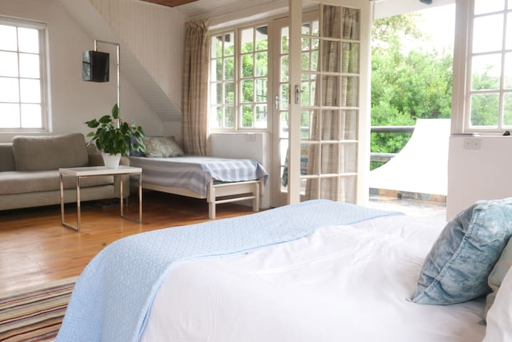 Doors onto the balcony, corner couch area with stacked single beds/ day bed
