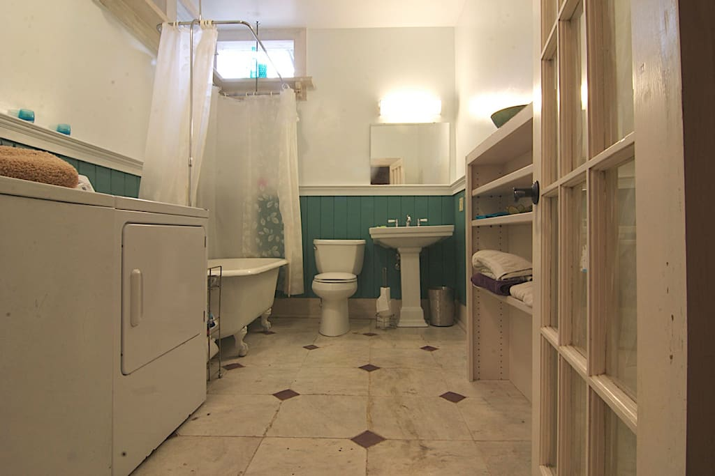 Private bathroom with clawfoot bathtub and W/D in the master bedroom