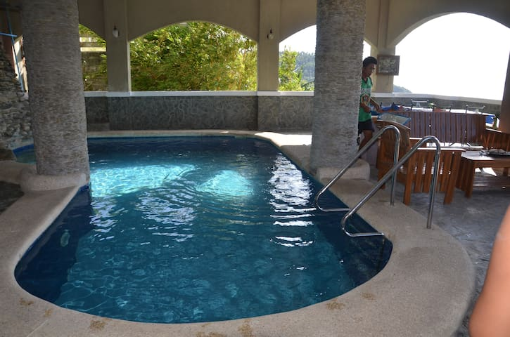 Private swimming pool with wooden table and chairs plus bbq grill