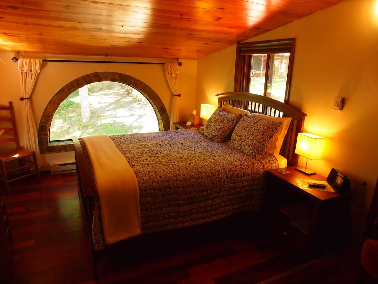 Queen walnut bed looking out through the stone arch window into the woods.