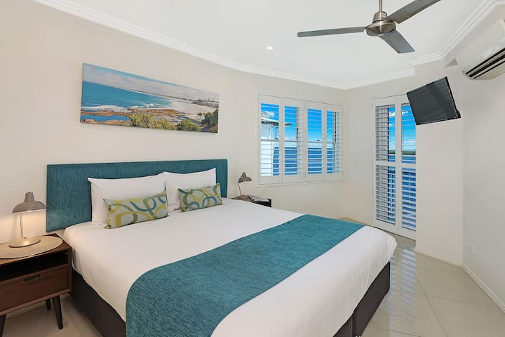 """Master bedroom where you can enjoy the water views from bed. Plantation shutters with block-out blinds means that even """"dark as a cave"""" sleepers can enjoy their sleep-in. Ceiling fan and air-conditioner ensure you stay comfortable all year round."""