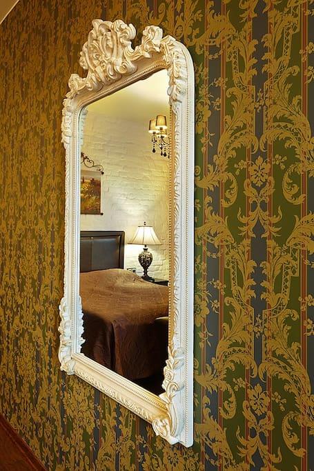 Зеркало с видом на кровать и прикроватную лампу