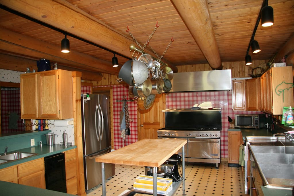 Fully equipped kitchen with a gas stove, griddle for flapjacks, triple sink, large cutting board island and a single sink. Everything the discerning chef would love to have.