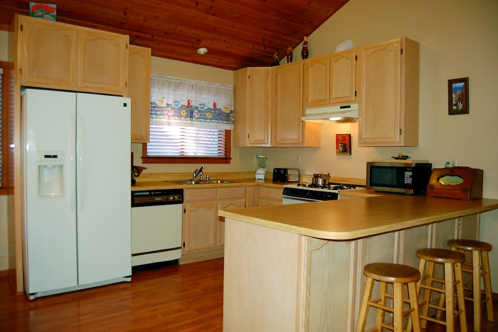 Kitchen with a gas stove, dishwasher and additional seating for three