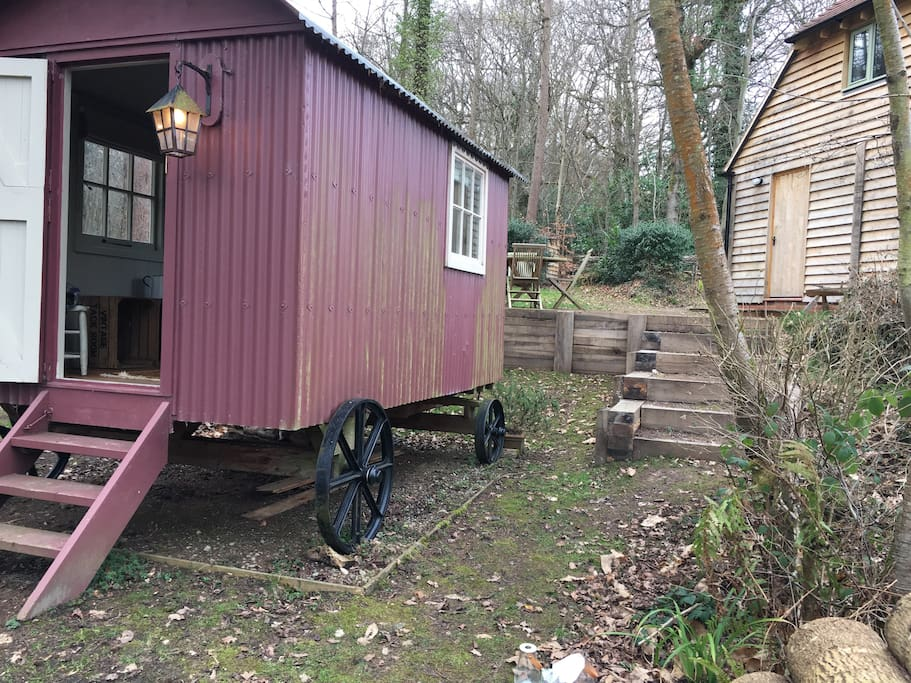 The shepherd's hut with steps up to the barn house in the background.