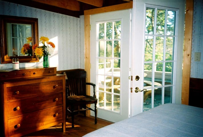 The main bedroom with queen bed, antique dresser & large closet. Large private deck with treed view. Drapes have been added.
