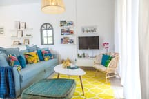 The living room is stylishly decorated in exotic turquoise and yellow gold tones.