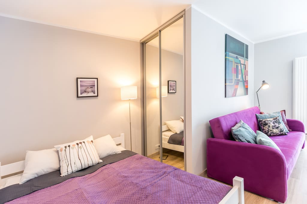Comfortable double bed on the right and big wardrobe with the mirrors