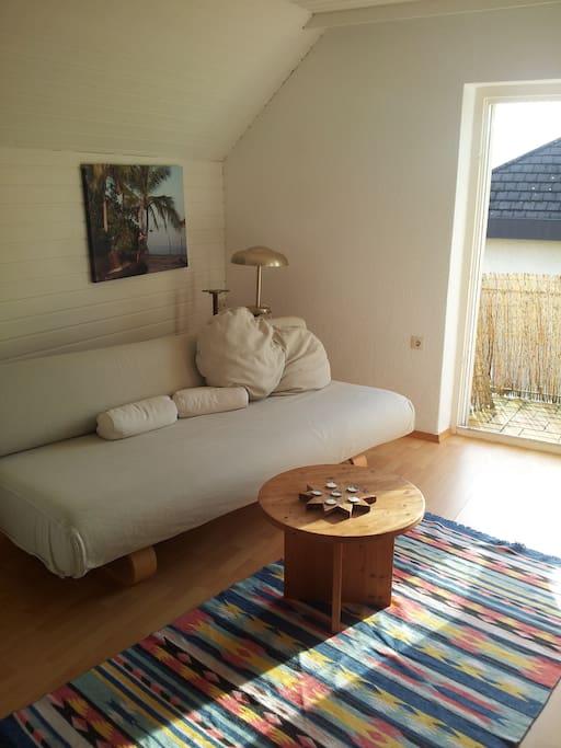 Wohnzimmer mit Schlafcouch und Balkon