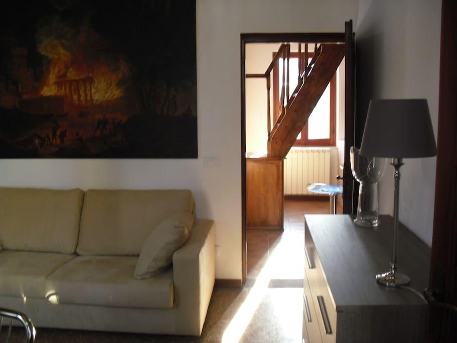 Il soggiorno con uno scorcio sulla scala che porta alla terrazza sul tetto, detta altana.
