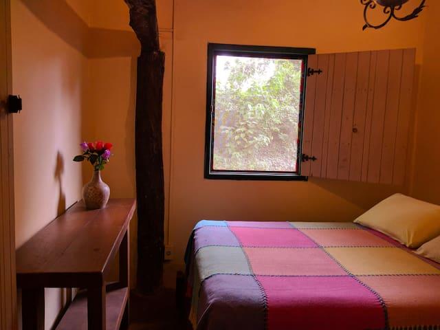 Quarto 2 com uma cama de casal e um aparador.