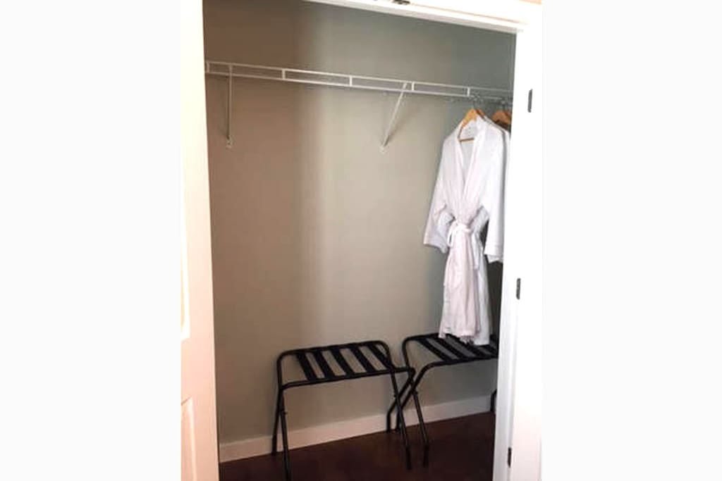 Large closets with luggage racks, robes and wood hangers.
