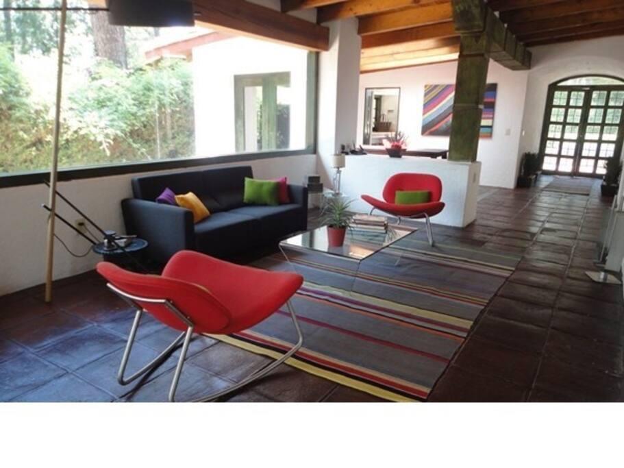 Sala y comedor con ambientes eclécticos  y juveniles. Al fondo, puerta principal.