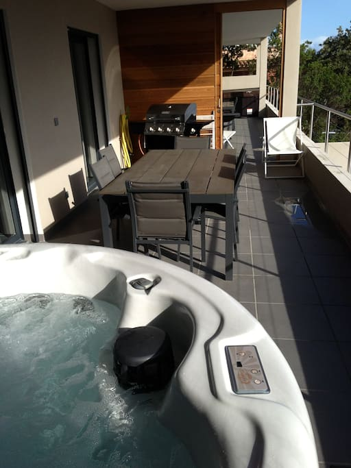 grande terrasse avec barbecue, jacuzzi, transats, table et chaise