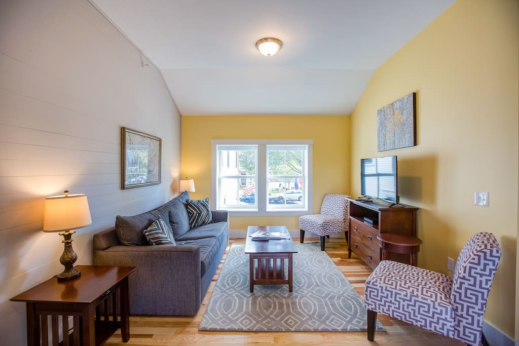 """Bright and comfortable living room with queen size sleeper sofa.  40"""" Smart TV with Roku, Netflix and cable.  Great views of Main Street!"""