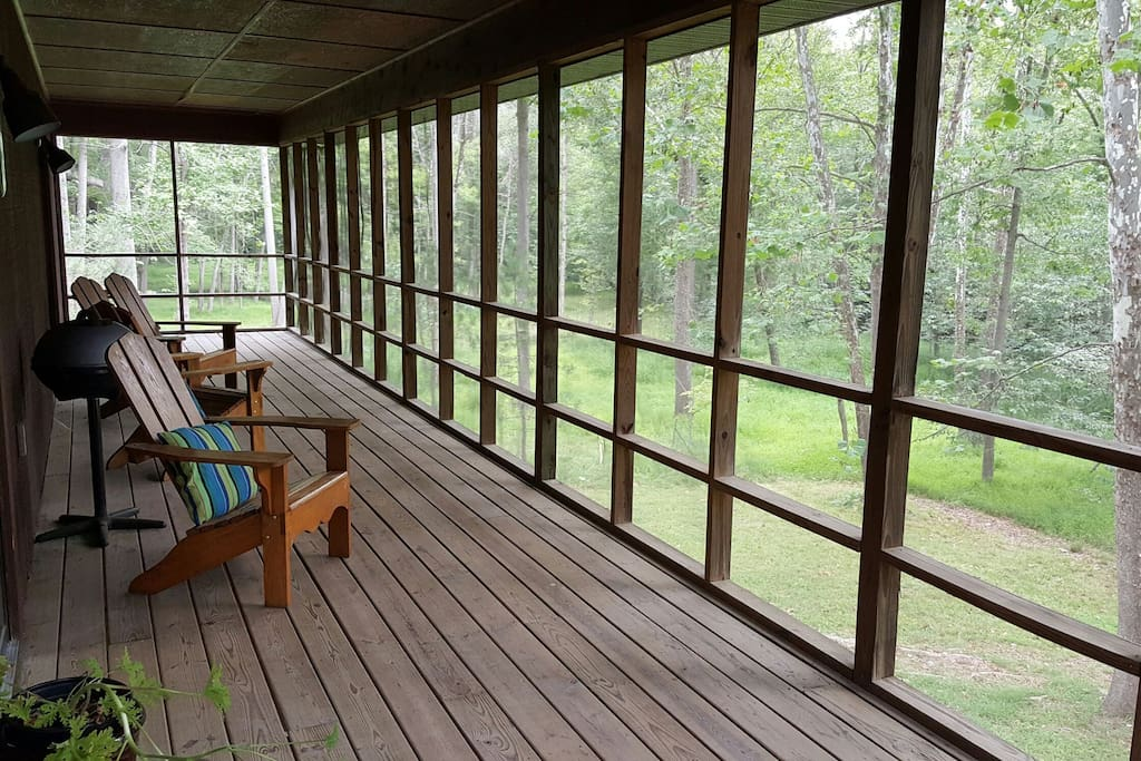 Large screened deck looks out across backyard and to the river.
