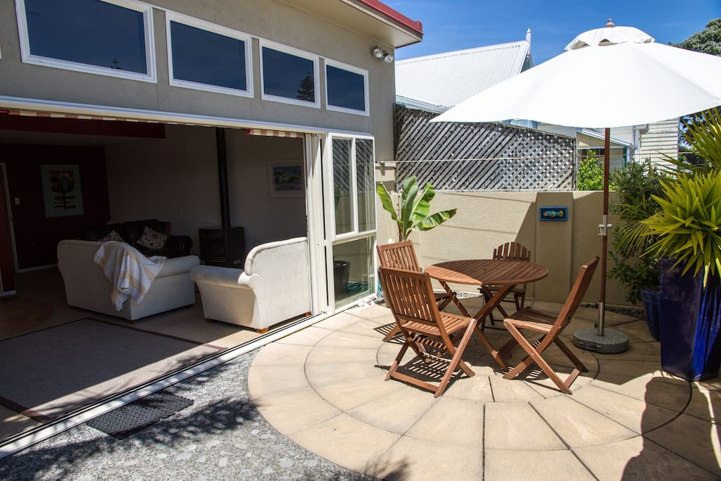 Sunny courtyard, Table & chairs, sun umbrella. Doors opening into lounge & kitchen area.