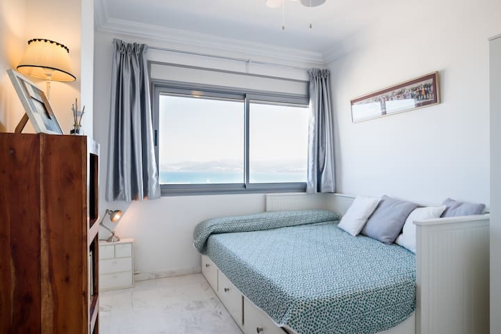 The second bedroom. Look out the window to see, again, the nice SEA VIEW. 2 twin beds together. We can prepare them as 2 separate beds or as 1 big one.   It has tons of storage, ceiling fan, A/C and heater. Total confort