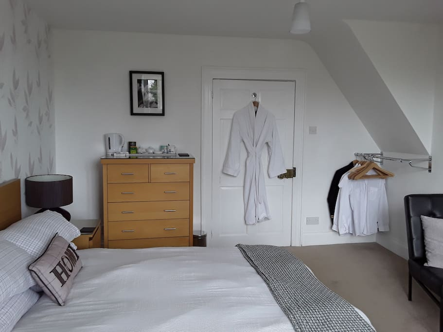 A nice relaxing bedroom contains Clothes rail,Chest of draws,bedside cabinets,table and chairs. Double bed. TV Chair and footstool.