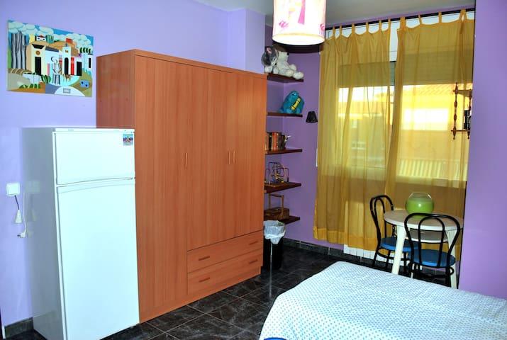 Dormitorio de dos camas con nevera