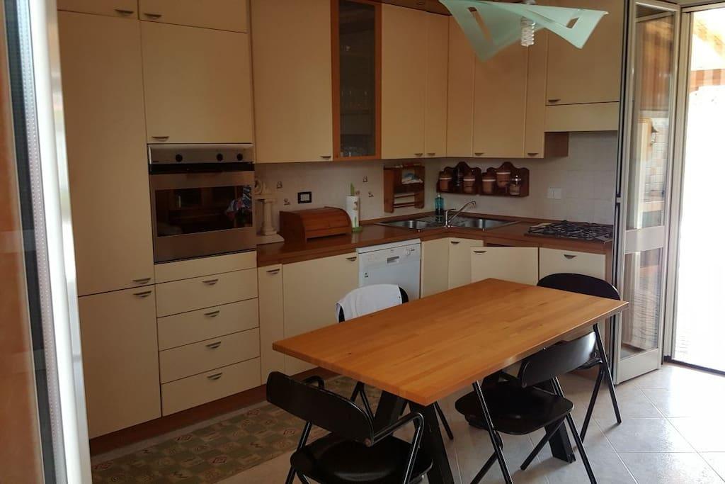 Cucina soggiorno dotata di lavastoviglie, tavolo centrale con parete attrezzata a muro con divano