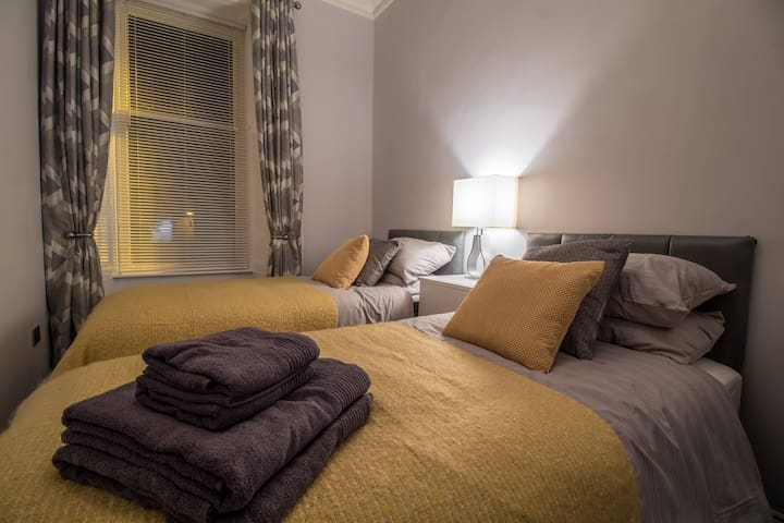 Cosy and modern bedroom two, with two single beds.