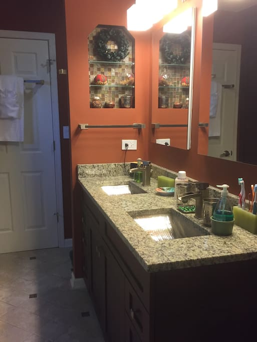 The recently remodeled bathroom has a granite countertop with two hammered-nickel sinks, a walk-in Roman shower, and a big soaking tub.