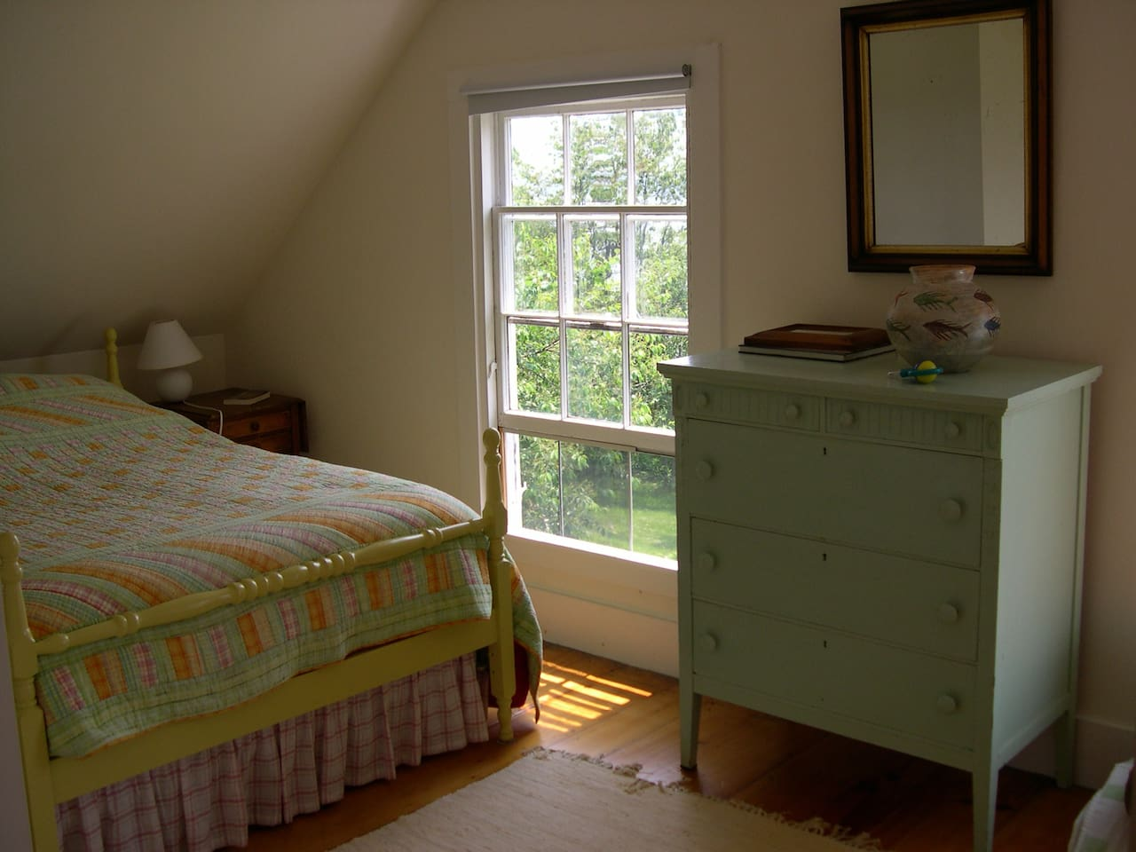 The guest bedroom, desk is to the left; to the right of the bureau is a rocking chair and another window.